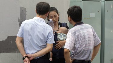 Yuan Shanshan, wife of detained Chinese lawyer Xie Yanyi, is questioned by security staff near the Tianjin court.