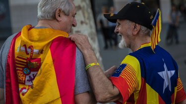 Two men, one wearing a Spanish flag, left, and the other wearing an estelada' or independence flag, talk during Spain's National Day in Barcelona on Thursday.