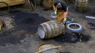 A distillery staff member works on a whisky barrel in Scotland, which has become the first country to set a minimum price on booze.