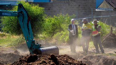 Detective Superintendent Des Bray (left) inspects the dig site at a factory in Plympton, Adelaide.
