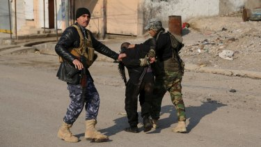 Iraqi security forces arrest a suspected fighter with the Islamic State group during a military operation to regain control of the eastern side of Mosul, Iraq.