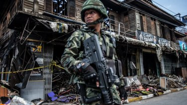 Soldiers on alert at the burnt out bombed remains of a traditional timber shop.