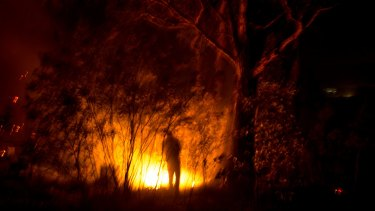 Long, hot summer: Adam Watkin douses spot fires near his home on Three Chain Road near Lancefield in Victoria.