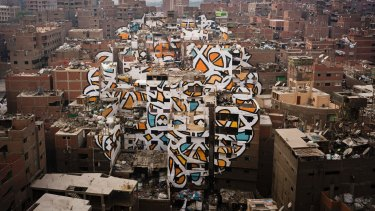 A mural stretched across more than 50 buildings by the artist eL Seed, in the poor Manshiyat Nasser district of Cairo.