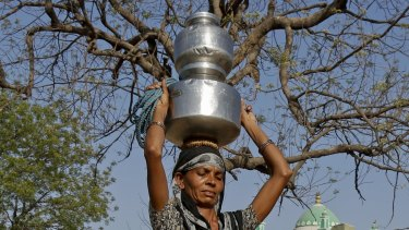 An Indian woman carries pitchers filled with drinking water collected from a well at Gibpura village on the outskirts of Ahmadabad, Gujarat state, India.