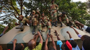 Zimbabweans reach out to touch and thank soldiers, for the army's role in Mugabe's demise.