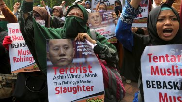 Muslim women, holding a poster depicting Wirathu, the leader of Myanmar's nationalist Buddhist monks, raise their fists outside Myanmar Embassy in Jakarta, Indonesia.