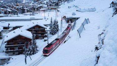 The first passenger train is leaving the train station towards Taesch, in Zermatt, Switzerland.
