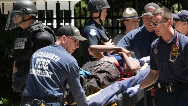 Paramedics rush a stabbing victim away on a gurney, after members of right-wing extremists groups holding a rally outside the California state Capitol building in Sacramento clashed with counter-protesters, authorities said.