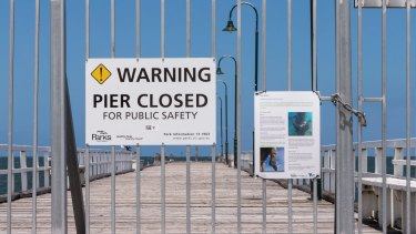 Warning signs on Kerferd Road pier where it is partially closed.