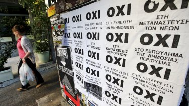 "A woman walks past referendum campaign posters reading ""No"" in Greek in Athens."
