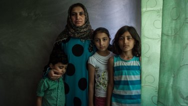 Basma poses for a portrait with her children Nour, Osama and Assadullah in the apartment her family now shares in Sanliurfa, Turkey.