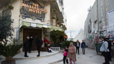 People pass the Walled Off Hotel and the wall in Bethlehem, in the Israeli-occupied West Bank.