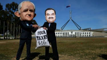 Protestors wearing suits resembling Prime Minister Malcolm Turnbull and Adani chief Gautam Adani take part in a protest in Canberra on Thursday.