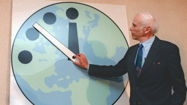 Leonard Rieser, chairman of the Board of the Bulletin of the Atomic Scientists and a member of the Manhattan Project, moves the minute hand to 11:51pm in 1998.