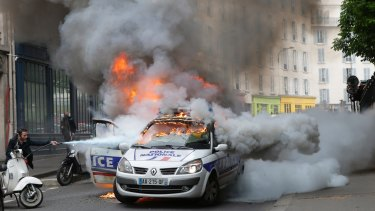 A man tries to put out fire on a burning police car during  protests against a labour reform in May in Paris.
