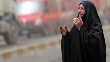 A woman grieves at the scene of a deadly suicide a car bomb in the Parada neighbourhood of Baghdad.