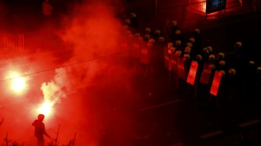 Provocative: A protester taunts the police as several hundred masked men broke away from a far-right march and threw stones and flares at lines of riot police in Warsaw.