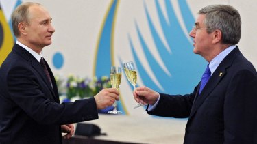 Russian President Vladimir Putin, left, toasts a glass of champagne with IOC boss Thomas Bach in 2014.