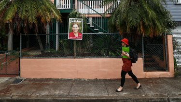 Greens candidate for South Brisbane Amy MacMahon walks past a corflute of Deputy Queensland Premier Jackie Trad.