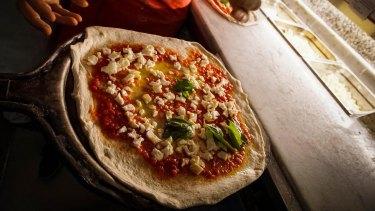 A Neapolitan 'pizzaiuoli' (pizza makers) prepares a pizza, in Naples, Italy,