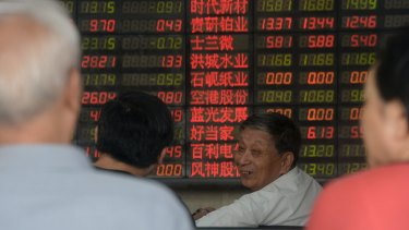 Who is to blame? Investors chat in front of an electronic board showing stock information at a brokerage house in Shanghai.