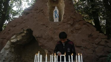 A boy lights candles at the Holy Family Catholic Church in Srinagar, Indian controlled Kashmir.