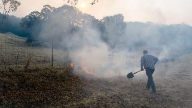 Gilman Clark, a longtime resident of Wooden Valley, takes a shovel to burning grass along a fence line next to a vineyard on Wednesday.