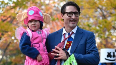 Justin Trudeau takes his youngest son Hadrien, dressed as Paw Patrol character Skye, trick-or-treating.