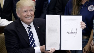 President Donald Trump holds up a signed executive order giving businesses expanded authority to design their own apprenticeship programs.
