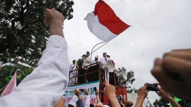 Muslim protesters raise their fists as the leader of Islamic Defenders Front, Rizieq Shihab, gives a speech during a protest against Jakarta's ethic Chinese and Christian governor Basuki Tjahaja Purnama.