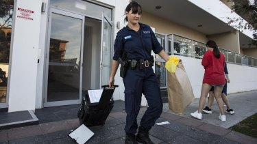 A police officer removes evidence from Michelle Leng's Campsie home.