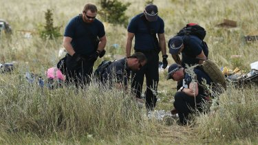 Australian Federal Police officers and their Dutch coutnerparts collect human remains from the MH17 crash site in the fields outside the village of Grabovka in the self proclaimed Donetsk Republic, Ukraine.