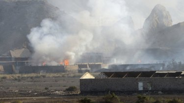 Buildings at the Jabal al-Hadid military camp burn after air strikes in Aden, Yemen, on Saturday.