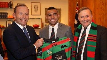 Former prime minister Tony Abbott presents a South Sydney NRL Jersey to Nathan Merritt.
