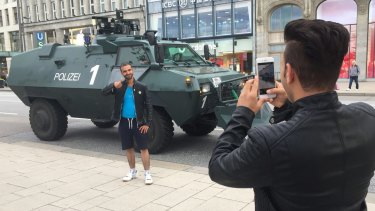 People take photos with police vehicles in Hamburg ahead of G20.