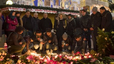 People light candles as floral tributes sit in Berlin Christmas market in Berlin days after a terror attack in December.