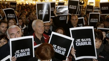 """People hold posters reading """"I am Charlie"""" as they gather to express solidarity with those killed in an attack at the Paris offices of weekly newspaper <i>Charlie Hebdo</i>,"""