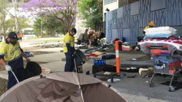 Brisbane City Council workers clear out the site of a homeless 'township' beneath the Go Between Bridge.