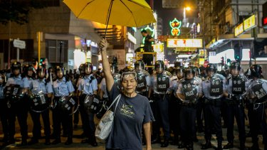 A pro-democracy activist holds a yellow umbrella in front of a police line on a street in Hong Kong's Mong Kok district on November 25 last year.
