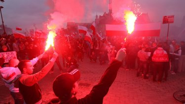 Several thousand right-wing nationalists wave Polish flags and burn flares as they march through Warsaw.