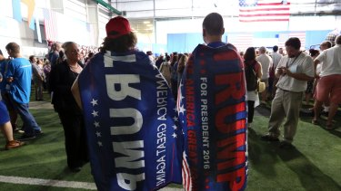Two Trump supporters are pretty much ignored as they wear Donald trump capes at a campaign rally for Democratic presidential candidate Hillary Clinton  in Pennsylvania.