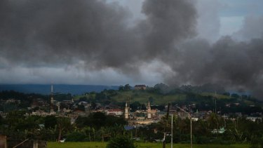 Black smoke from continuing military air strikes rises above a mosque in Marawi.