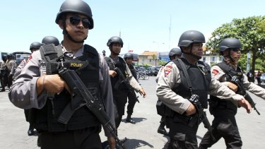 High alert: Police officers patrol New Year's celebrations in Bali on Thursday.