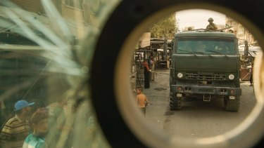 Russian soldiers who convoyed a group of journalists move on a truck in the city of  Deir Ezzor, Syria.