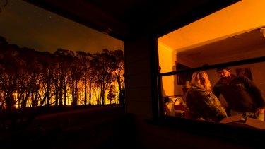 Adam Watkins and partner Prue Mathiesen in their kitchen taking a break after fighting a bushfire that threatened their home near Lancefield, Victoria, in October.