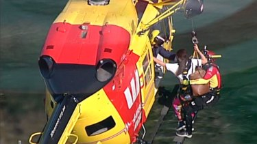 The Westpac Rescue Helicopter winches two girls to safety from the rocks at North Head, near Manly.