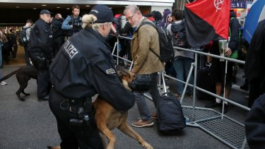 Police monitor protesters who have arrived in Hamburg to rally against the G20.