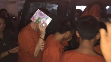 Tammy Davis-Charles hides her face as she is led back to her jail cell from Phnom Penh court on Thursday.