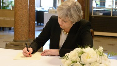 Prime Minister Theresa May signs a condolence book in Manchester. The Tories have taken a dip in the polls since last week's bombing.